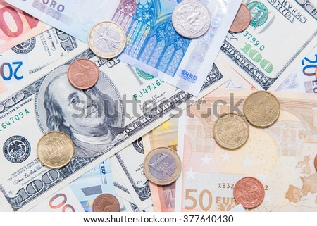 American hundred dollar bills and different Euro bills on background. - stock photo