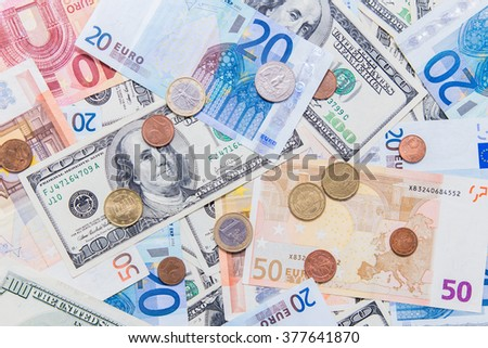 American hundred dollar bills and different Euro bills on background. Cent and eurocent coins upon the money background. - stock photo