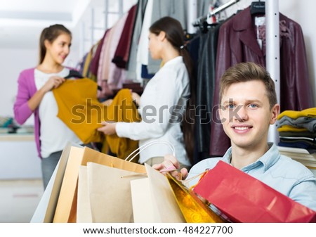 american husband sitting with purchases, wife buying more clothes