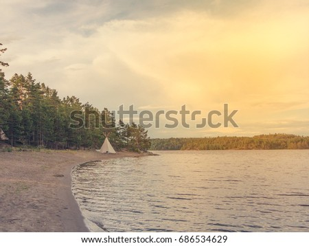 American Indian tent tipi on the shore of a lake by the forest & American Indian Tent Tipi On Shore Stock Photo 686534629 ...