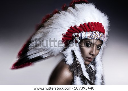 native american man wearing headdress shooting bow and