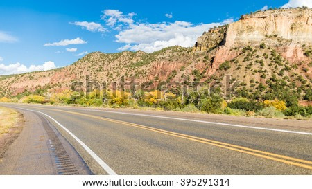 American landscape across long endless asphalt mountain road in beautiful sunny, Colorado, USA