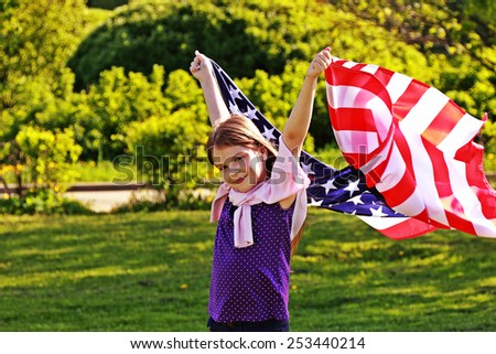American little girl holding a large American flag. Image with instagram filter.