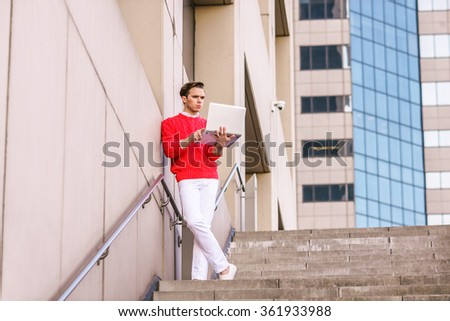 American Man reading, working remotely on laptop computer, wearing red knit sweater, white pants, standing on stairs against wall outside office building in New York, narrowing eyes, thinking hard.  - stock photo