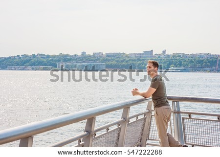 American Man summer vacation in New York. A young guy wearing green T shirt, beige pants,  standing by metal fence by Hudson River in New York opposite New Jersey, looking. Color filtered effect