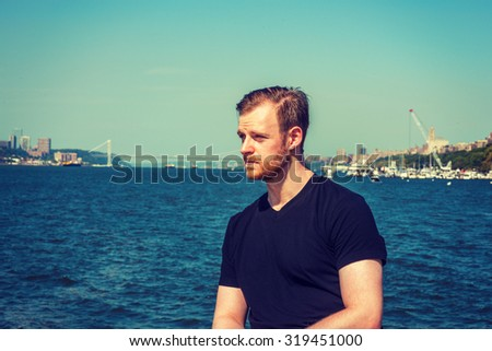 American man traveling in New York. Wearing black v neck T shirt, a young guy with beard, mustache standing by Hudson River, looking forward. Bridge, harbor on background. Instagram effect.  - stock photo