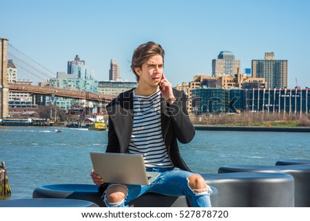 American man travels, works in New York, wearing fashionable long coat, striped undershirt, ripped broken hole jeans, frowned, works on laptop computer, calls on cell phone.