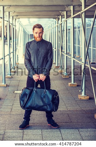 American man with beard, mustache traveling in New York, dressing in black, shirt, pants, shoes, carrying leather bag, standing on sidewalk bridge, looking at you. New Yorker casual street fashion.