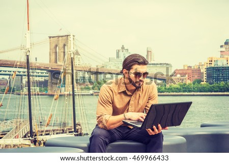 American man with beard traveling, working in New York, wearing brown shirt, sunglasses, sitting on bench by river, hunching back, reading on laptop computer. boat on background.
