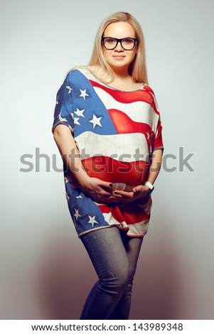 American Mom Concept: Portrait of a smiling young pregnant woman in american flag like dress and trendy glasses holding her belly and posing over gray background. Hipster style. Studio shot - stock photo