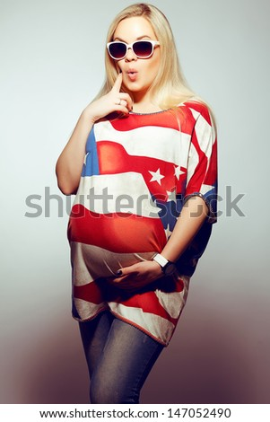 American Mom Concept: Surprised young pregnant woman in american flag like dress and trendy sunglasses posing over gray background. Hipster style. Studio shot - stock photo