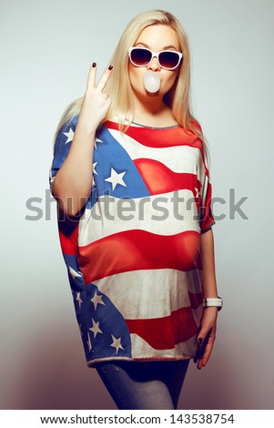 American Mom Concept: Young pregnant woman in american flag like dress and trendy sunglasses chewing bubble gum and showing V (victory symbol) sign. Hipster style. Studio shot - stock photo