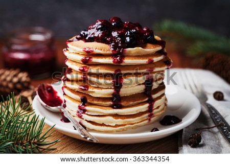 American pancakes or fritters served with strawberry and blueberry jam, delicious dessert for breakfast in winter, rustic style - stock photo