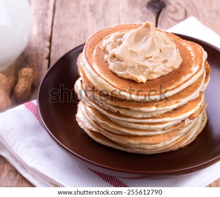 American pancakes with Peanut Butter on wooden background - stock photo