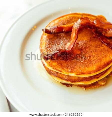 American pancakes with syrup and crispy bacon - stock photo