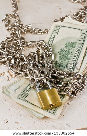 american paper money with a silver chain and a closed gold lock - stock photo