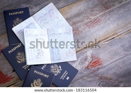 American passports lying on a rustic wooden table open to reveal hand stamps from customs officials on border control applied during traveling abroad - stock photo