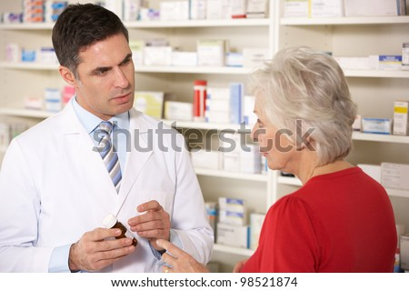 American pharmacist with senior woman in pharmacy - stock photo