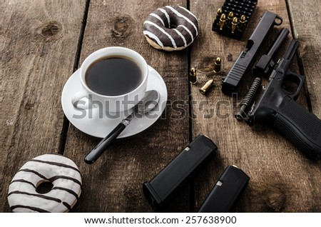 American police officer morning, donuts, juice, fresh black coffee and his gun - stock photo