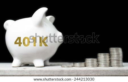 American retirement savings concept with piggy bank and coins against black background - stock photo
