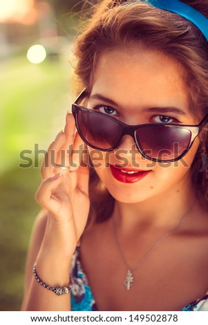 American retro girl in suglasses. Photo in 60s style. - stock photo