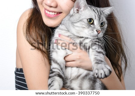 American short hair cat is held by  a girl