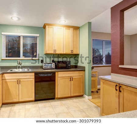 American small house or apartment type typical kitchen for 2014. Tile floor, birch tree light wood cabinets, black color applicances
