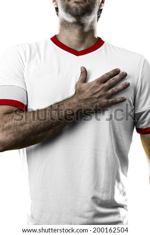 American soccer player, listening to the national anthem with his hand on his chest. On a white background. - stock photo