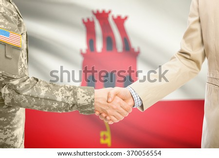 American soldier in uniform and civil man in suit shaking hands with national flag on background - Gibraltar - stock photo