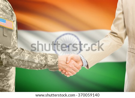 American soldier in uniform and civil man in suit shaking hands with national flag on background - India - stock photo