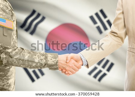 American soldier in uniform and civil man in suit shaking hands with national flag on background - South Korea - stock photo