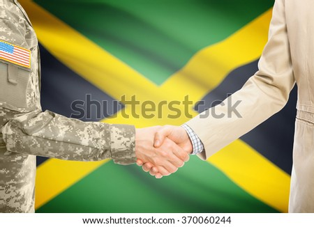 American soldier in uniform and civil man in suit shaking hands with national flag on background - Jamaica - stock photo