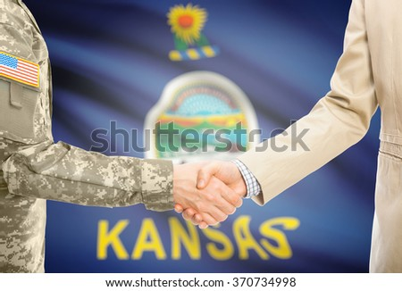 American soldier in uniform and civil man in suit shaking hands with USA state flag on background - Kansas - stock photo