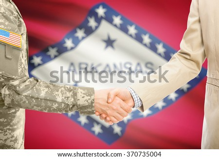 American soldier in uniform and civil man in suit shaking hands with USA state flag on background - Arkansas