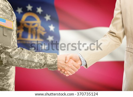 American soldier in uniform and civil man in suit shaking hands with USA state flag on background - Georgia