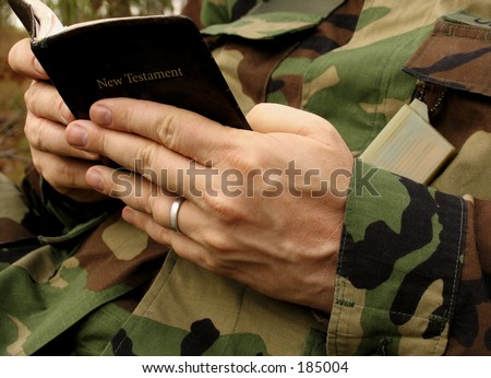 american soldier's hands in uniform reading Bible - stock photo