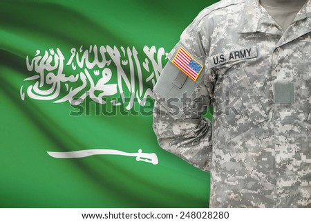 American soldier with flag on background - Saudi Arabia - stock photo
