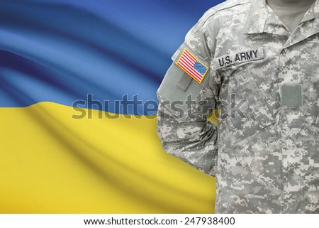 American soldier with flag on background - Ukraine - stock photo