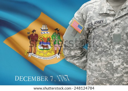American soldier with US state flag on background - Delaware - stock photo