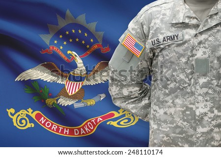 American soldier with US state flag on background - North Dakota - stock photo