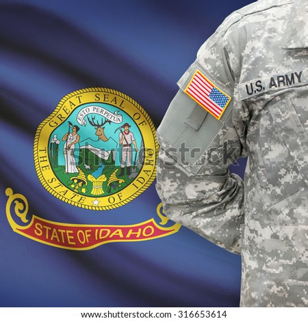 American soldier with US state flag on background series - Idaho - stock photo