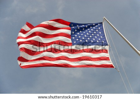 American state flag flying in the wind, with blue sky and clouds in the background