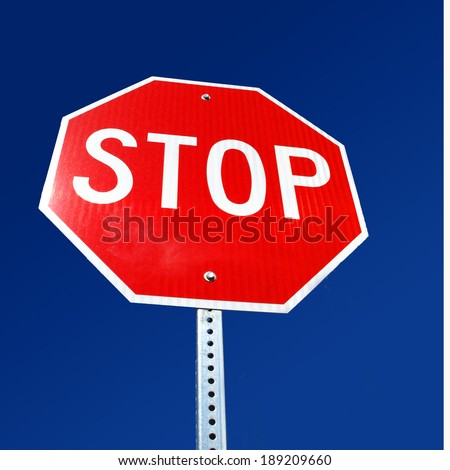 American stop sign on road with blue sky as warning to vehicle drivers