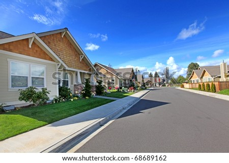 American street of new development with rambler homes. - stock photo