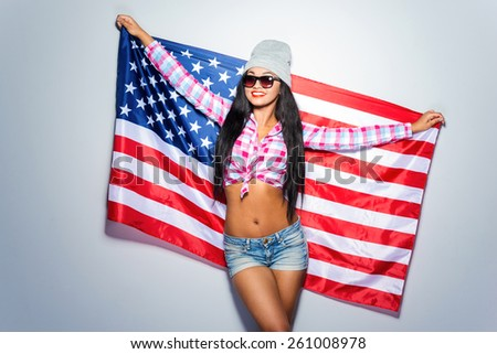 American teen. Beautiful young black woman carrying American flag and smiling while standing against grey background - stock photo