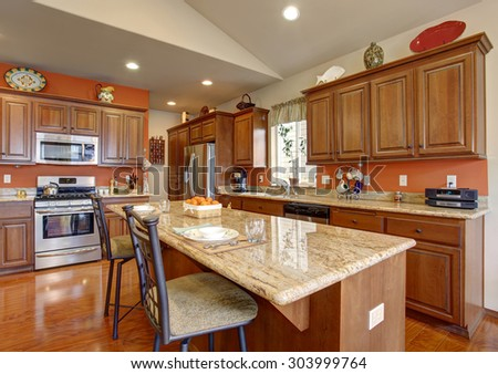 American traditional kitchen with glossy hardwood floor, and an island. - stock photo