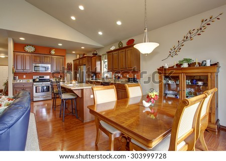 American traditional kitchen with glossy hardwood floor, and great dinning room. - stock photo