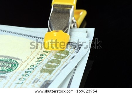 American US one hundred dollar bills money squeezed tight in a clamp isolated on black background - stock photo