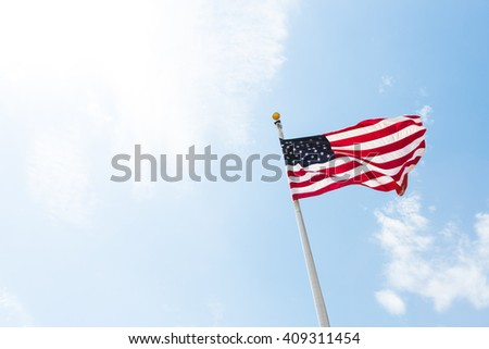 American USA flag :red, white and blue, stars and stripes) blowing in the wind on a flagpole against blue bright sunny skies - stock photo