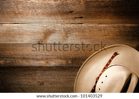 American West authentic white straw cowboy hat on old and aged western saloon floor wood plank background